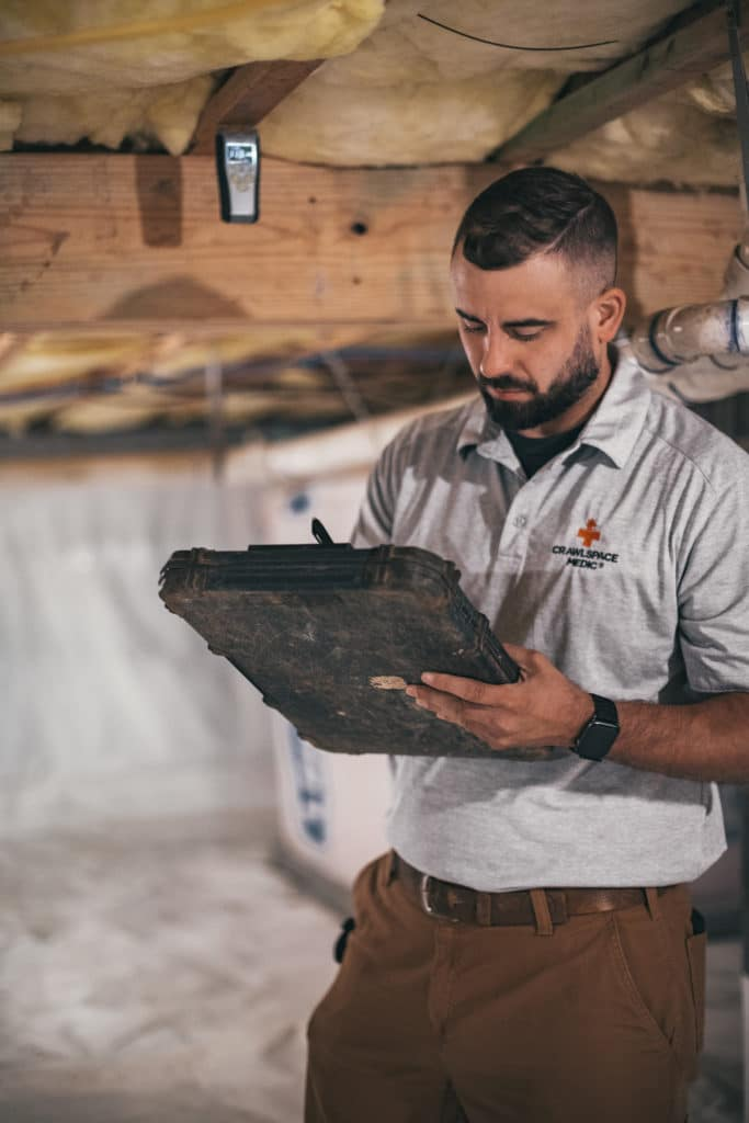 crawl space technician checking work for quality
